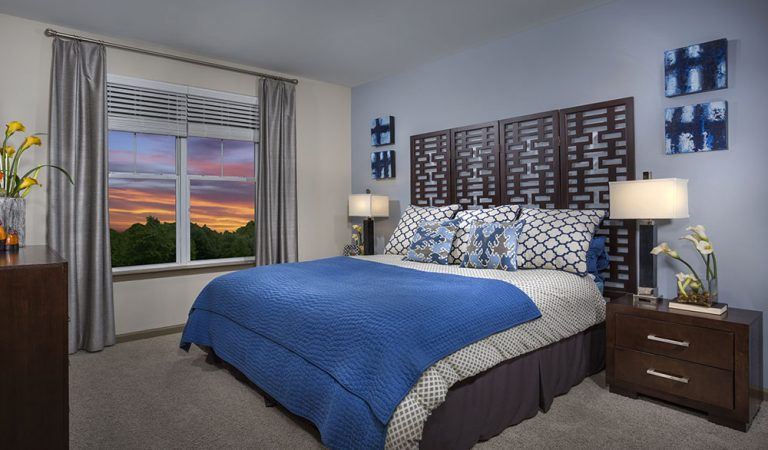 The Bowen apartments in Bowie, MD bedroom with king size bed and blue bedspread with view out window at sundown